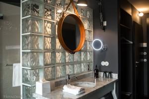 Der runde, mit Ledergurten umrandete Spiegel über dem Waschbecken ist ein von Gubi im Stil von Jacques Adnet nachgebauter Designklassiker.