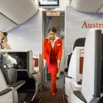 Hier zeigt die Stewardess, wo es zu den Notausgängen geht.