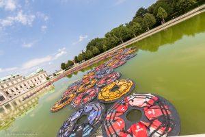 Angeordnet wie ein kalligrafisches F schwimmen die 201 Ringe aus jeweils fünf Westen wie Lotusblüten auf dem Wasser des barocken Bassins.